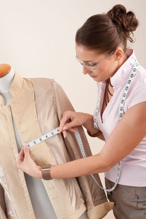 textile designer: Female fashion designer taking measurement of jacket at studio
