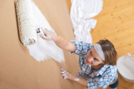 Home improvement: Young woman painting wall with paint roller photo