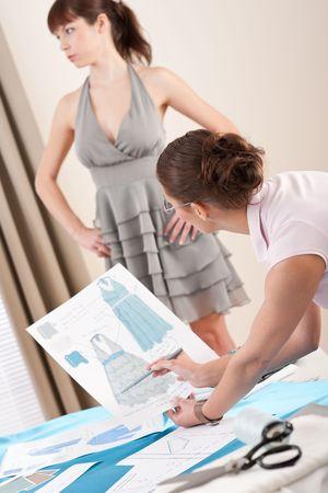 work material: Model in gray dress fitting by female fashion designer studio Stock Photo