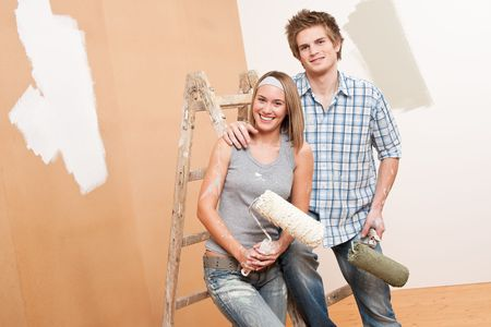 Home improvement: Young couple painting wall with paint roller photo