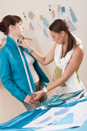 fitting: Female fashion designer measuring turquoise jacket on model, taking measurements Stock Photo