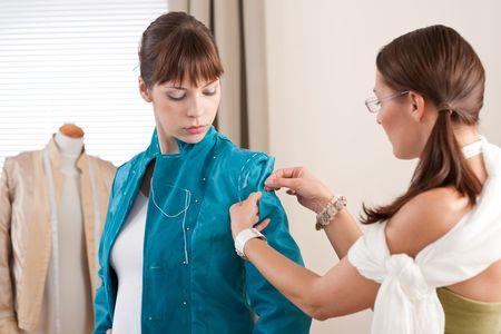 Model fitting by professional female fashion designer studio photo