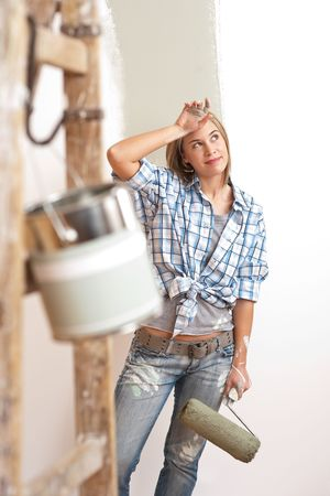 paint can: Home improvement: Young woman with paint roller and ladder Stock Photo