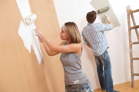 decorando: Inicio de mejora: joven pareja pared de pintura con rodillos de pintura