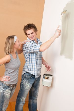 Home improvement: Man painting wall with paintbrush holding paint can photo