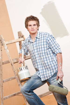 Home improvement: Young man with paint roller, paint can and ladder photo
