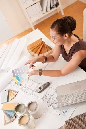 tervező: Female interior designer with color swatches and laptop at office