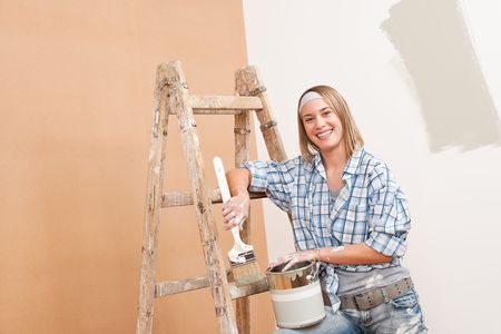 Home improvement: Smiling woman with paint and brush painting wall photo