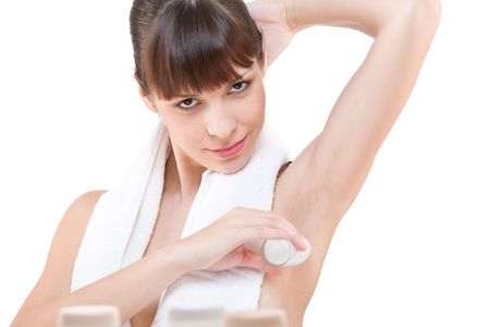 Body care: Young woman applying deodorant on white background photo