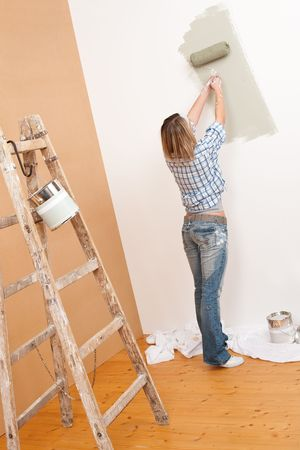 Home improvement: Cheerful woman with paint roller and ladder painting wall photo