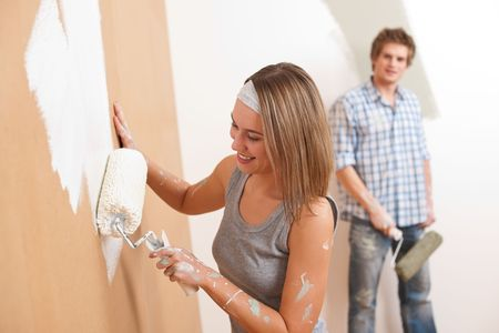 Home improvement: Young man and woman painting wall with paint roller photo