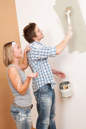 man painting: Home improvement: Man painting wall with paintbrush holding paint can