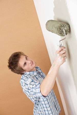 Home improvement: Young man with paint roller painting wall photo