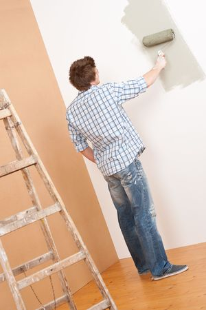 Home improvement: Young man with paint roller and ladder photo