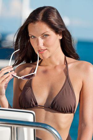Young woman sailing on luxury yacht sunbathing in bikini photo