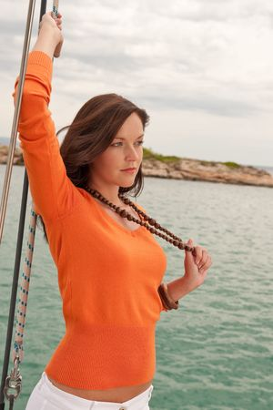 Attractive woman sailing on luxury yacht holding rope photo