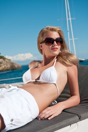 Blond woman sunbathing on luxury yacht with bikini and sunglasses photo