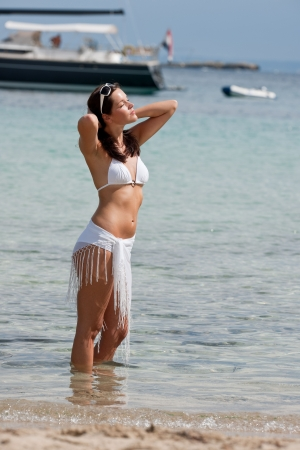 Young attractive woman standing in the sea sunbathing on the beach photo