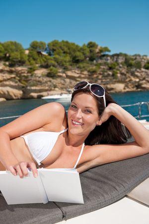 Attractive woman sunbathing on luxury boat reading book in bikini photo