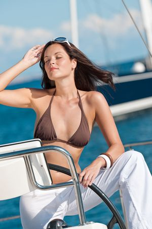Young woman sailing on luxury yacht sunbathing in bikini photo
