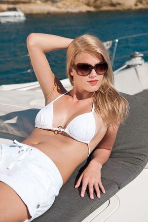 Blond woman sunbathing on luxury yacht with bikini and sunglasses photo