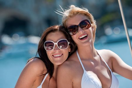 Two attractive smiling woman on sail yacht having fun on sunny day photo