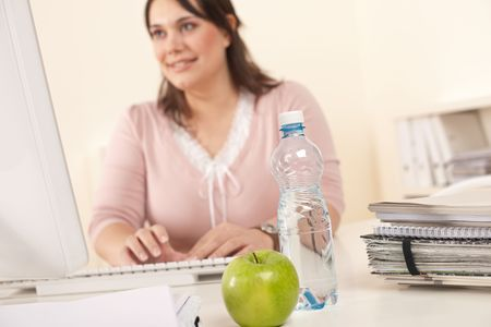 Young businesswoman working at office, focus on apple and bottle of water on table Stock Photo - 6327412