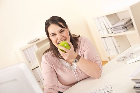 Young businesswoman biting apple at modern office Stock Photo - 6327409