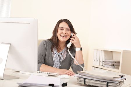 secretary woman: Smiling young woman working on the phone at office