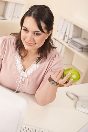 Young happy businesswoman holding apple at office having snack photo