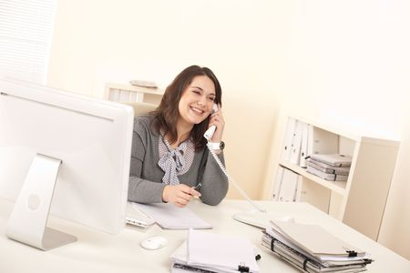 Young executive woman talking on phone at office in front of computer photo