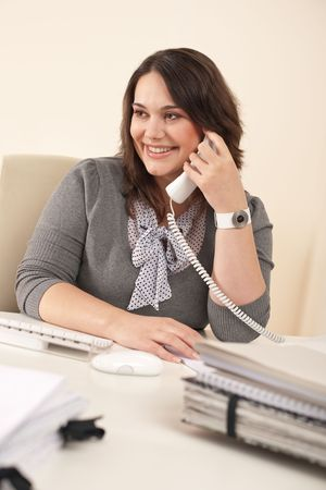 Smiling secretary on phone at modern office sitting at desk photo