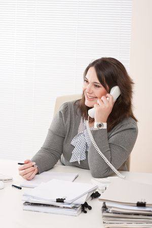Smiling young business woman working on the phone at office photo