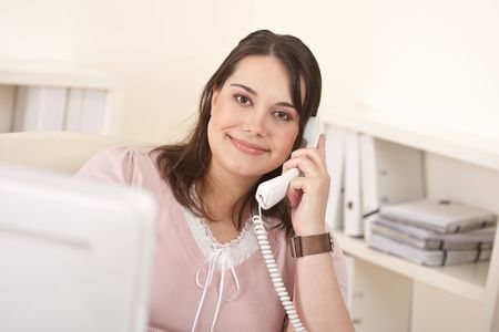 Portrait of attractive executive woman at office on phone photo
