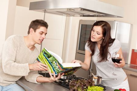 Young couple in kitchen choosing recipe from cookbook drinking red wine Stock Photo - 6497934