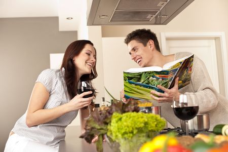 Young couple in kitchen choosing recipe from cookbook drinking red wine Stock Photo - 6497965