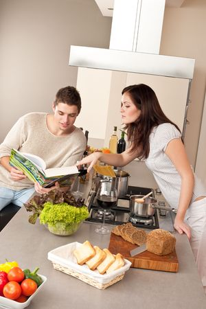 Young couple cooking in kitchen together with cookbook Stock Photo - 6498005