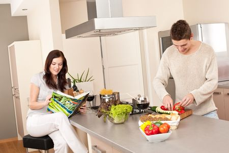 Young couple cooking in kitchen together with cookbook Stock Photo - 6498009