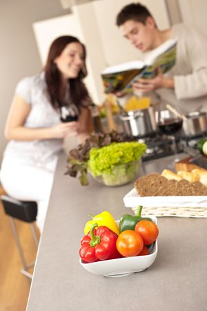 Young couple in kitchen choosing recipe from cookbook drinking red wine Stock Photo - 6498008