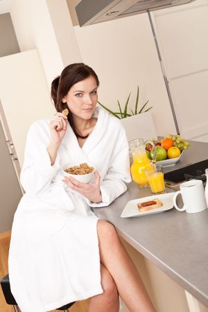 Happy woman in bathrobe eating healthy cereals for breakfast in kitchen Stock Photo - 6418655
