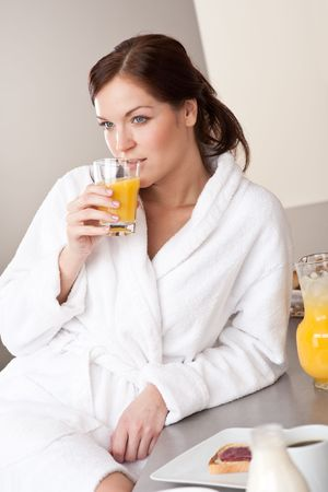 Young woman enjoying orange juice and breakfast in modern kitchen photo