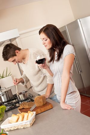 Young couple cooking in kitchen together drinking red wine Stock Photo - 6418659