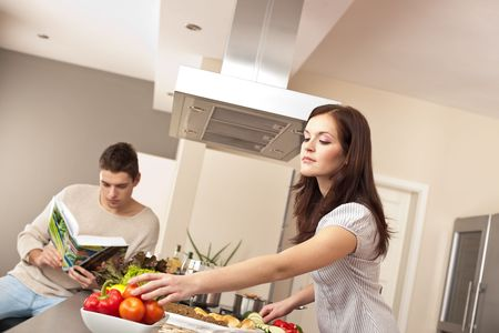 Young couple cooking in kitchen together with cookbook Stock Photo - 6418662