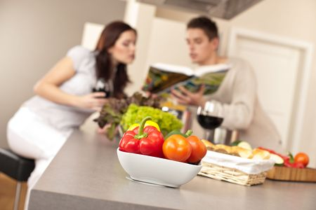 Young couple in kitchen choosing recipe from cookbook drinking red wine Stock Photo - 6418642