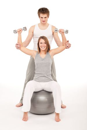 Young healthy couple training with weights and fitness ball on white photo