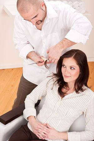 Professional male hairdresser comb female customer at salon photo