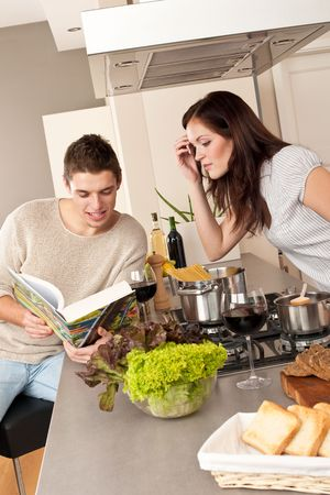 Young couple cooking in kitchen together with cookbook Stock Photo - 6418680
