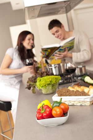 Young couple in kitchen choosing recipe from cookbook drinking red wine Stock Photo - 6418684