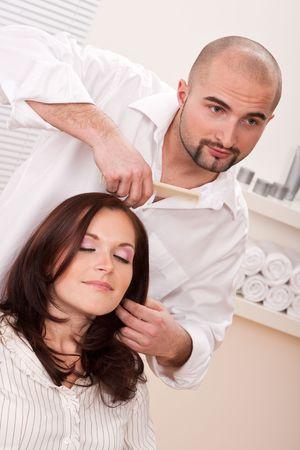Professional male hairdresser comb female customer at salon photo