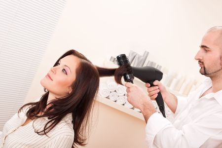 Professional male hairdresser with hair dryer and hair brush at salon with female customer photo